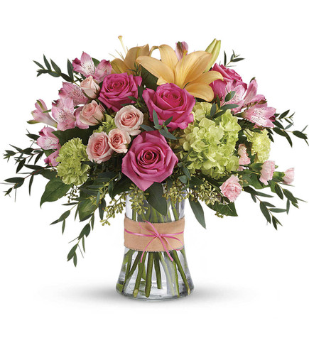 Blushing in Potomac showcases green hydrangea, hot pink roses, pink spray roses, peach asiatic lilies, pink alstroemeria, green carnations, pink miniature carnations, seeded eucalyptus and lemon leaf in glass gathering vase in Rockville MD, Palace Florists
