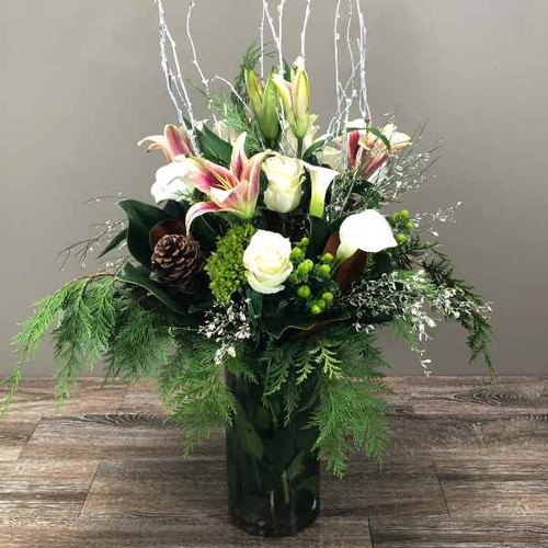 Holiday Happenings showcases white roses, white callas, stargazers, pinecones, white branches, seasonal greens and more hand-designed in a tall cylinder vase in Rockville MD, Palace Florists