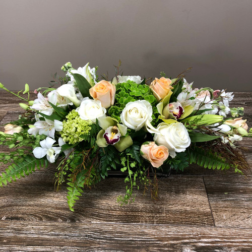 Gift from the garden showcases white roses, peach roses, green cymbidium orchids, dendrobium orchids, green hydrangea and beautiful foliage in a low container in Rockville MD, Palace Florists