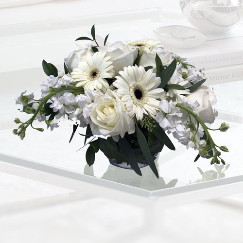 Sweet year centerpiece showcasing white roses, white gerbers, white stock and beautiful foliage in a glass bubble bowl in Rockville MD, Palace Florists
