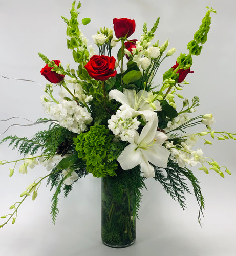 Merry and Bright in DC showcases red roses, bells of Ireland, white lilies, green hydrangea, white stock and white dendrobium orchids surrounded by seasonal greens in glass vase in Washington DC, Palace Florists