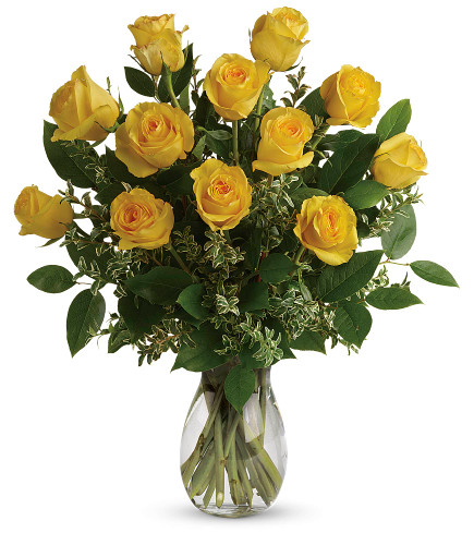 One dozen yellow royal roses accented with wax flower, coils of bear grass and beautiful foliage in clear glass vase in Washington DC and Rockville MD, Palace Florists