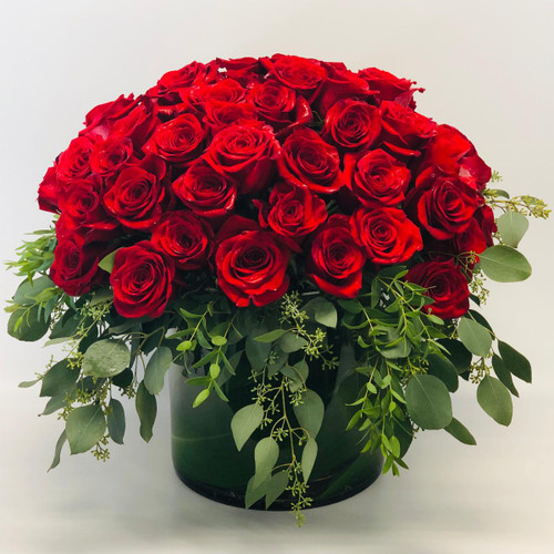 Beyond Romance is 4 dozen ruby red roses tightly design in a large cylinder in Bethesda MD, Palace Florists