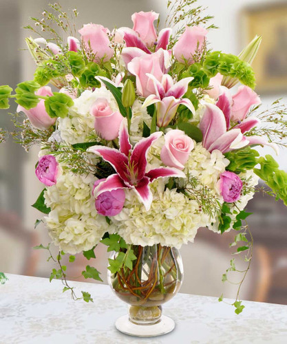 True Love features a dozen pink roses along with stargazer lilies, peonies and Bells of Ireland atop a bed of hydrangeas in a tall vase in Rockville MD, Palace Florists