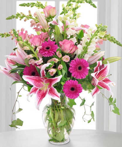 Sweet Kisses showcases pink gerbers, pink roses, lilies, and more in a beautiful glass vase in Chevy Chase MD, Palace Florists