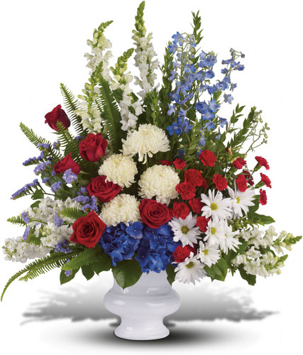 With Distinction showcases  beautiful mix of all-American red, white and blue flowers such as hydrangea, roses, miniature carnations, snapdragons, chrysanthemums and more are perfectly arranged in a white urn in Washington DC and Rockville MD, Palace Florists