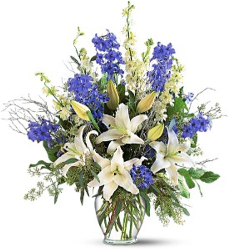 Sapphire Miracle showcases delphinium, larkspur, lilies and eucalyptus in a clear glass vase in Rockville MD, Palace Florists