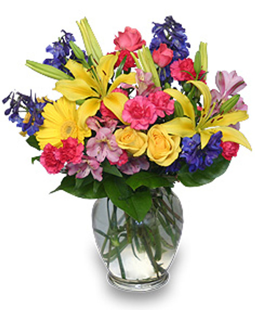 Rainbow of blooms is delivered without contact and showcases gerber daisies, yellow roses, delphinium, hot pink mini carnations, pink spray roses, pink alstroemeria and foliage in a ginger vase in Rockville MD, Palace Florists