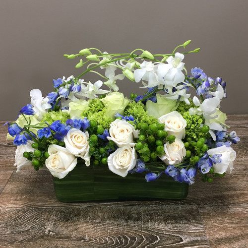Through the Clouds showcases white orchids, white roses, blue delphinium, green mini hydrangea and green hypericum berries in a leaf wrapped glass rectangular vase in Washington DC, Palace Florists
