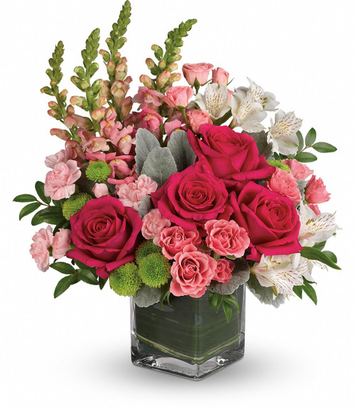Garrett Park Garden showcases hot pink roses, pink spray roses, white alstroemeria, pink miniature carnations, green button spray chrysanthemums, pink snapdragons with beautiful foliage in a leaf wrapped clear vase in Rockville MD, Palace Florists
