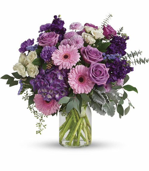 Magnificent Mauves feature purple hydrangea, lavender roses, crème spray roses, pink gerberas, lavender carnations, purple stock, lavender cushion spray chrysanthemums, lavender statice and foliage in a clear glass vase in Bethesda MD, Palace Florists