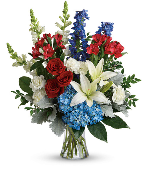 Colorful Tribute bouquet features blue hydrangea, red roses, white asiatic lilies, red alstroemeria, white carnations, blue delphinium, white snapdragons, huckleberry, dusty miller, aralia leaf and lemon leaf. Delivered in a gathering vase from Palace Florists in Rockville, MD