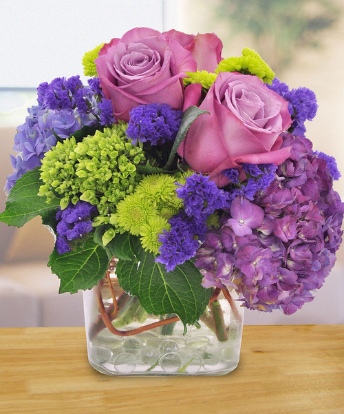 Purple Perfection features lovely lavender roses, purple and green hydrangeas and purple statice, along with green pompons and curly willow tips in a glass cube in Rockville MD, Palace Florists