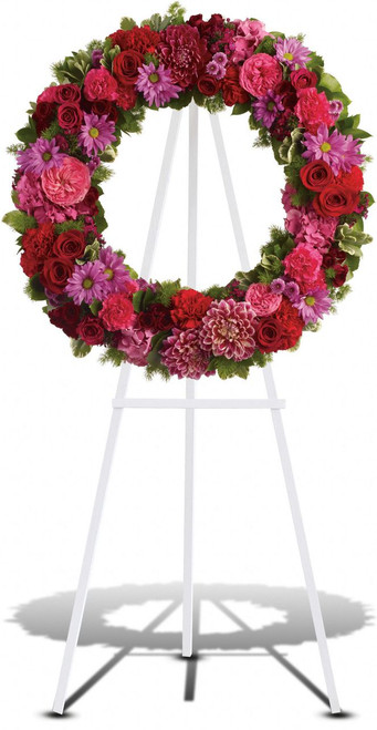 Infinite Love showcases pink hydrangea, hot pink roses and carnations, red roses, spray roses and carnations, burgundy dahlias, dark pink Sweet William, lavender daisy and button spray chrysanthemums along with fern and other fresh greens create a beautiful wreath on an easel in Washington DC and Rockville MD, Palace Florists