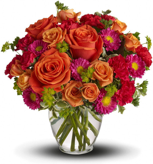 How Sweet It Is with a mix of hot pink, red and coral flowers such as roses, Matsumoto asters and carnations accented with greenery in a clear glass vase in Washington DC and Rockville MD, Palace Florists