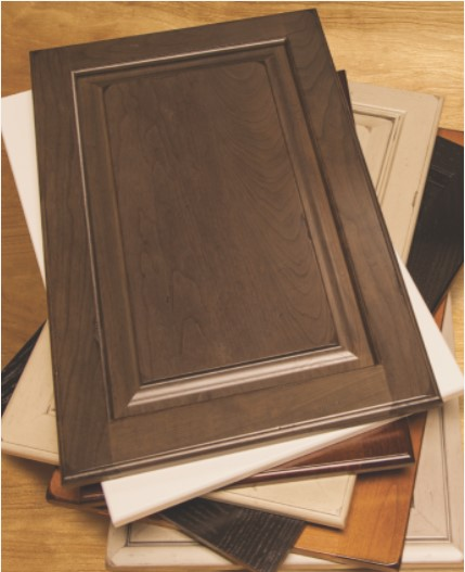 Stack of KraftMaid cabinet doors in various styles and finishes