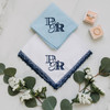 Powder blue men's handkerchief shown embroidered in navy thread with a custom designed monogram. The handkerchief is paired with the Navy lace handkerchief embroidered with the same custom designed monogram.