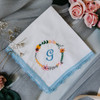 Something Blue handkerchief has embroidered floral wreath & bridal monogram. Handkerchief has blue lace trim & white fabric.