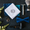 Groom wedding accessories including a white handkerchief with monogram in navy