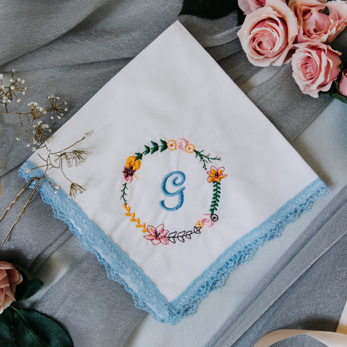 Something Blue handkerchief has embroidered floral wreath & bridal monogram. Handkerchief has blue lace trim & white fabric.