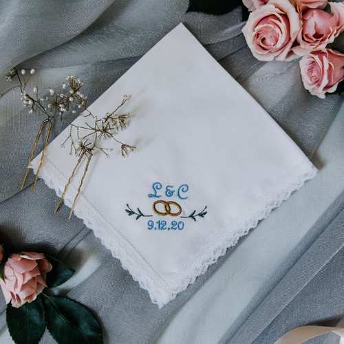 Something Blue Handkerchief with initials, wedding date and wedding rings.  It is embroidered in powder blue thread on a handkerchief with white lace trim.