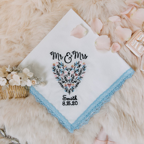 Something Blue handkerchief with embroidered name, date and floral heart. The handkerchief is white with powder blue lace and is shown with other bridal accessories.