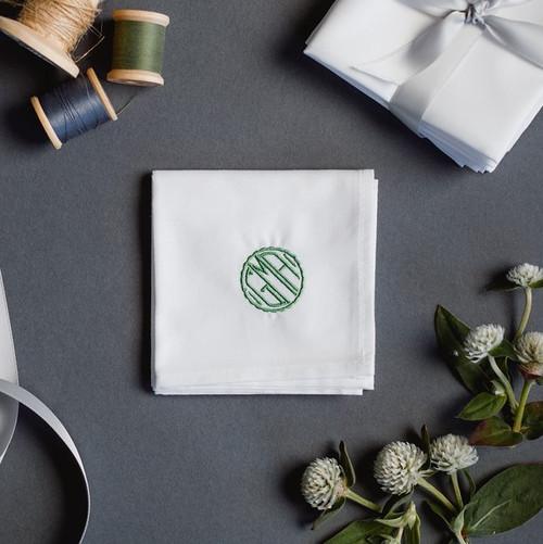 Men's monogrammed handkerchief with small circle monogram. The handkerchief is embroidered with a green monogram.