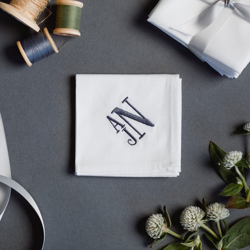 Monogrammed men's handkerchief with stacked embroidered monogram. The handkerchief is white with dark grey embroidery.