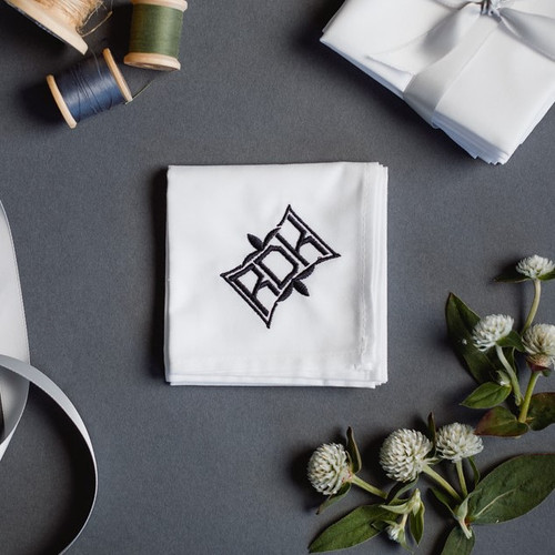 Men's monogrammed white handkerchiefs with fleur embroidered monogram style.  Handkerchief has black embroidery.