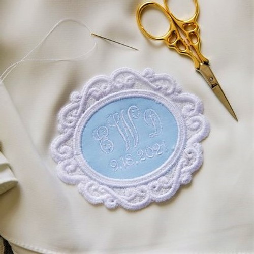 Monogrammed wedding dress patch in powder blue with white embroidery thread. Needle and thread for sewing into dress and scissors.