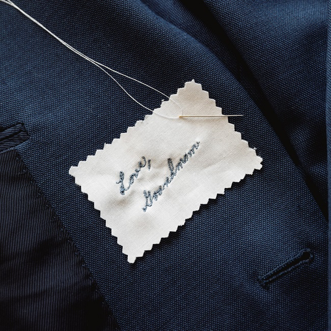 Handwriting embroidery for men's suit. Embroidery shown in smokey blue thread.