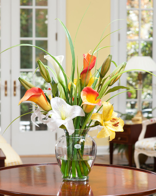 """Bright silk calla lily, day lily, silk flower accent and artificial grasses set in acrylic water in 7"""" glass vase"""