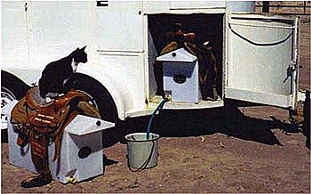 Dry Camp Water Tank and Saddle Rack; this water caddy maximizes space by storing 30 gallons of water while holding two saddles. Show in a typical setup being used in a bumper pull horse trailer's storage area.