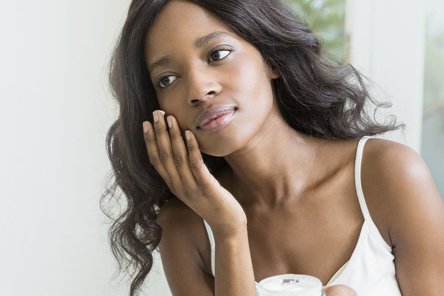 young woman applying moisturizer to her cheek