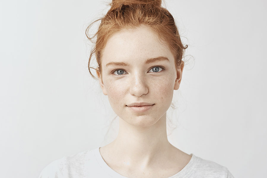 young woman with red hair and a faint smile