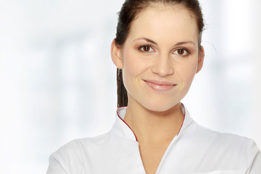 skin care professional in a white shirt smiling