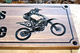 dirtbike rider carving on a wooden sign