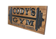 wooden gym sign with barbell