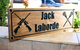 Wood carved sports sign with riffles and lacrosse sticks
