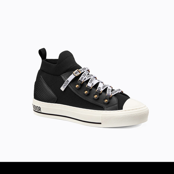 Cover photo of a Dior Walk'n'Dior Sneaker in Black. The shoe is made of technical mesh, has Dior signatures on its soles and laces.
