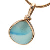 A bright aqua blue swoosh is suspended inside a paler aqua blue NATURAL and GENUINE sea glass piece from England. This is piece is set in our Original Wire Bezel© 14K Rolled Gold Setting that leaves this top quality sea glass TOTALLY UNALTERED from the way it was found on the beach in the UK.