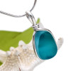 A beautiful Aqua mixed sea glass necklace pendant from the beaches of England where art glass scraps were tossed into the sea. This piece is set in our Original Wire Bezel© setting which leaves the sea glass totally unaltered from the way it was found on the beach!