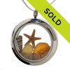 Sea glass in amber and rare gold combined with a real starfish, a tiny beach shell and beach sand in this one of a kind stainless steel locket necklace.
