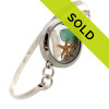 Flashed green genuine sea glass from England is combined with a fresh water stick pearl and real starfish in this stainless steel locket and presented on a solid sterling bangle bracelet