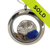 Simple small blue sea glass combined with a  sterling silver sandollar and small beach shells in this beach on the go stainless steel locket necklace.
