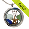 Blue , seafoam green and olive green sea glass pieces combined with a real starfish, a piece of seafan and beach sand in this sea glass locket necklace.