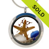 Blue, and pure white sea glass pieces combined with a real starfish, a piece of sea fan and beach sand in this sea glass locket necklace. Real beach sand from Florida completes your own personal beach on the go!