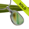 A beautiful mixture of vivid green and gold fused on a pure white sea glass piece. An unusual green that has a vivid stripe running through the center. This piece is set in our Original Wire Bezel© setting and leaves this amazing natural sea glass piece UNALTERED from the way it was found on the beach!