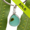 A beautiful very small piece of vivid aqua green sea glass set for a necklace in our Original Sea Glass Bezel© in solid sterling silver setting. Sorry this piece is no longer for sale.