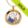 Blue sea glass with a small starfish and a small piece of vintage seafan set in a simple elegant goldtone locket